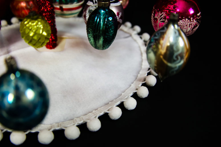 DIY mini tree skirt in white with a pompom trim (via tinselandtrim.com)