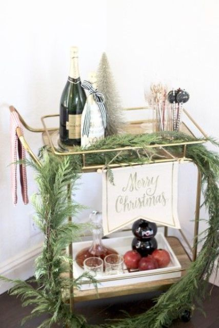 a bar cart with a lush evergreen garland, a tinsel Christmas tree and some drinks and pomegranates