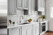 02 a chic light grey traditional kitchen with a white hexagon tile backsplash and a geometric rug