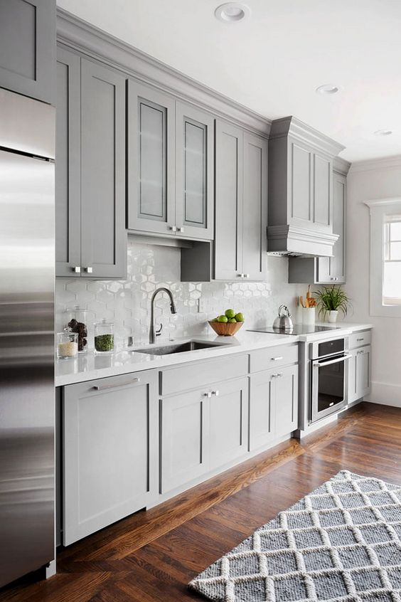 a chic light grey traditional kitchen with a white hexagon tile backsplash and a geometric rug