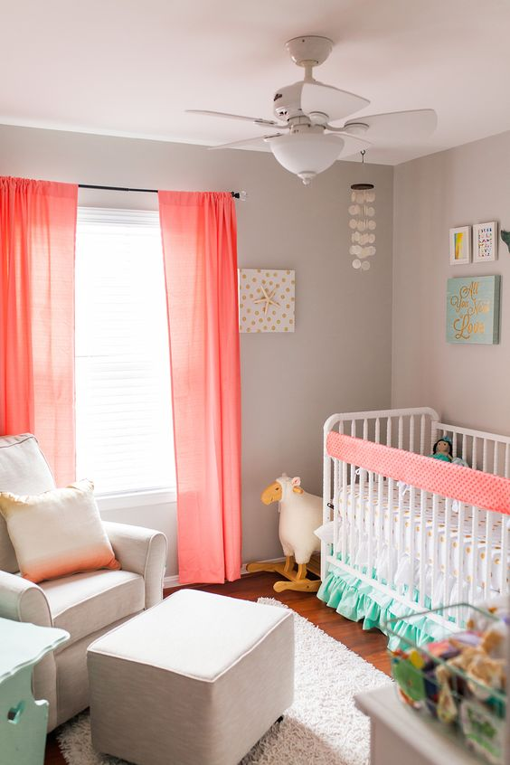 a coastal chic themed nursery spruced up with coral curtains, an ombre coral pillow and an accent on the bed