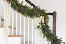 02 a lush evergreen Christmas garland with ribbon bows, pinecones and greenery touches to decorate the railing