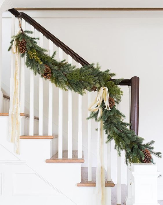 a lush evergreen Christmas garland with ribbon bows, pinecones and greenery touches to decorate the railing