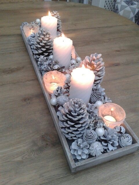 a whitewashed display with pinecones, beads and other stuff plus candles for a winter wonderland touch
