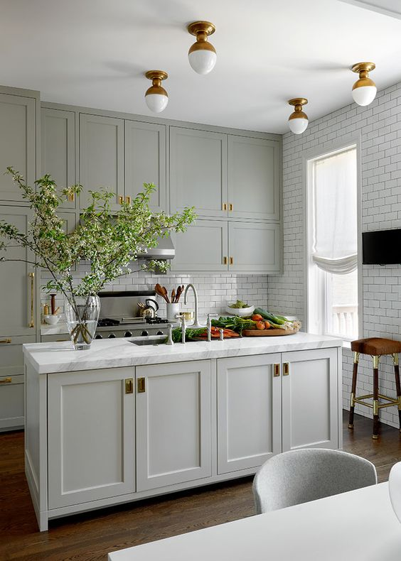 a classic dove grey kitchen with brass accents and vintage lighting plus white subway tiles