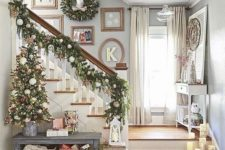 03 a lush evergreen garland for Christmas that is decorated with ornaments and continues the tree look on the stairs