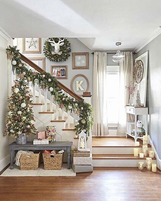 a lush evergreen garland for Christmas that is decorated with ornaments and continues the tree look on the stairs