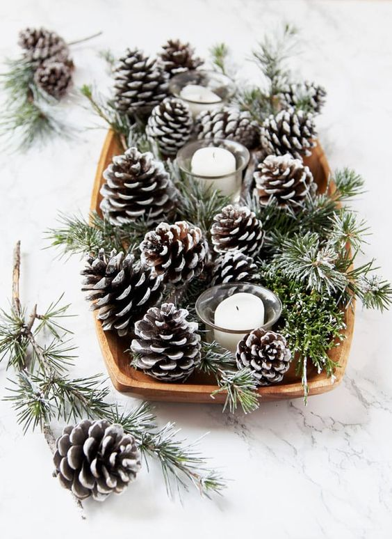 a simple and natural centerpiece of a dough bowl, snowy pinecones and evergreens and several candles for holidays
