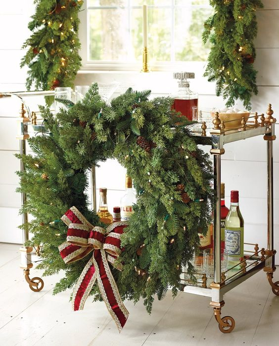 attach an oversized evergreen Christmas wreath with lights, ornaments and a large red bow
