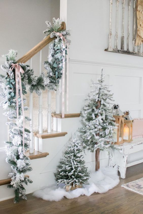 decorate your entryway with a flocked Christmas garland and a duo of Christmas trees plus faux fur