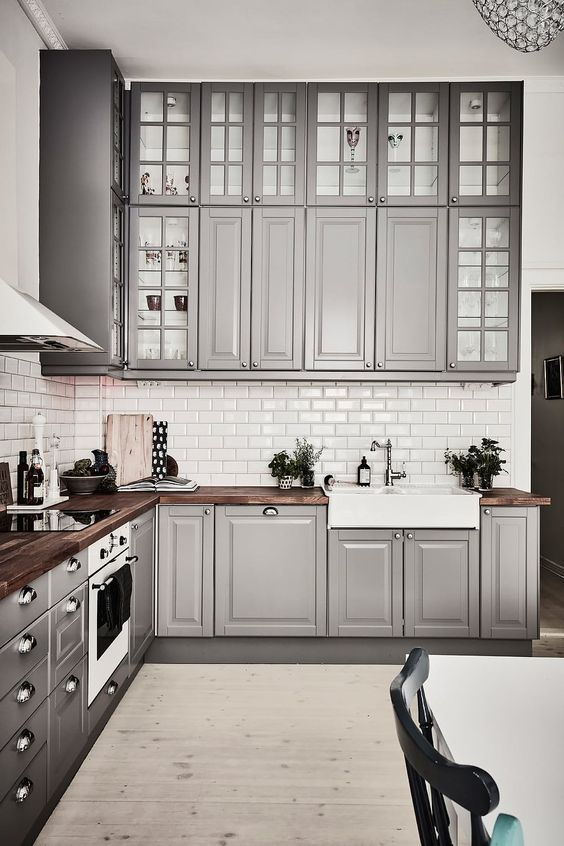 a cozy traditional grey kitchen with usual and glass cabinets, with rich-colored wooden countertops and metal knobs