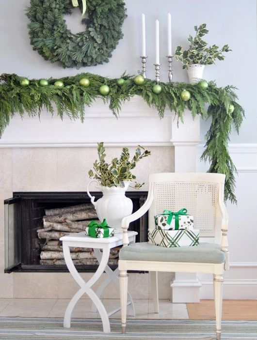 a lush evergreen garland with green ornaments for decorating a mantel and a matching wreath for holiday decor