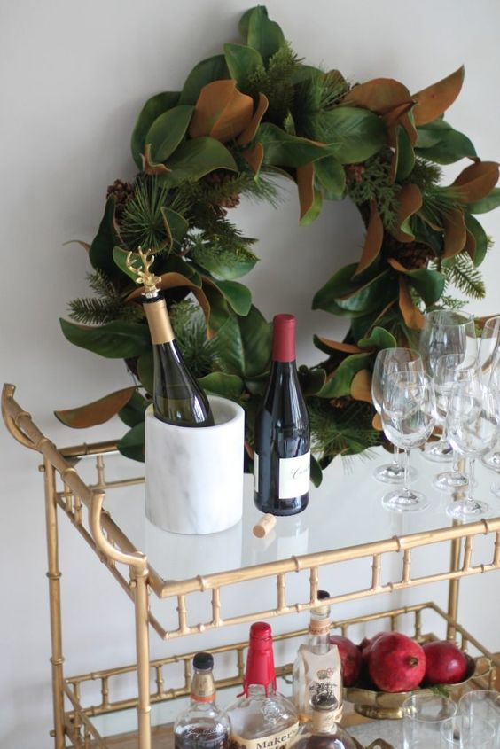 a Christmas bar cart with a lush foliage and evergreen Christmas wreath and pomegranates