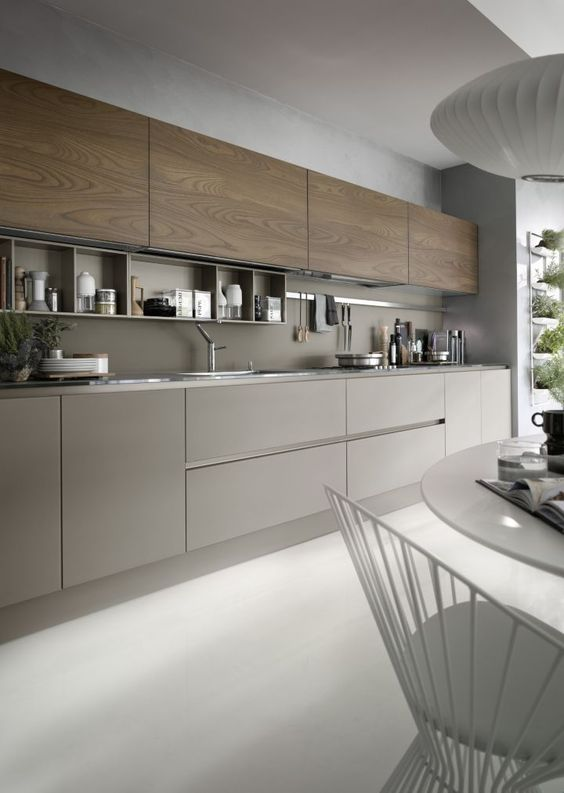 a grey kitchen with wooden cabinets and a grey backsplash, with built-in shelves and nickel touches looks very contemporary