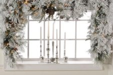 05 a snowy evergreen Christmas garland to cover a window, pinecones and lights add charm to the decor