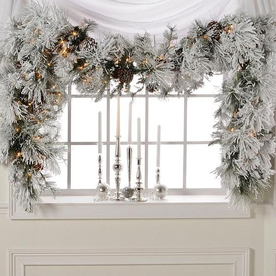 a snowy evergreen Christmas garland to cover a window, pinecones and lights add charm to the decor