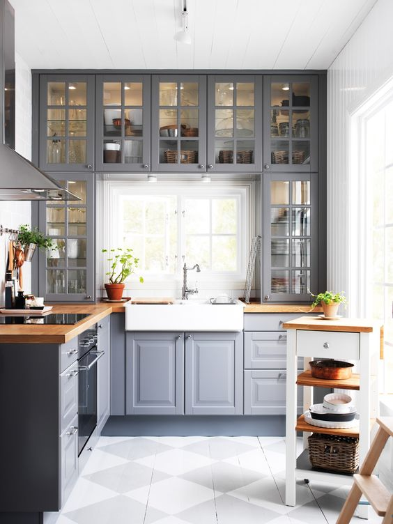 a grey kitchen with wooden countertops and whites and off-whites looks traditional meets modern