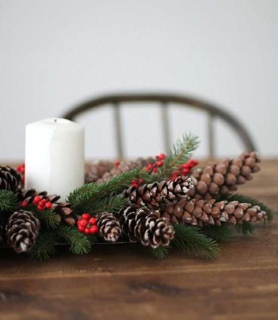 a tray with pinecones, berries, evergreens and a candle is a simple and natural centerpiece
