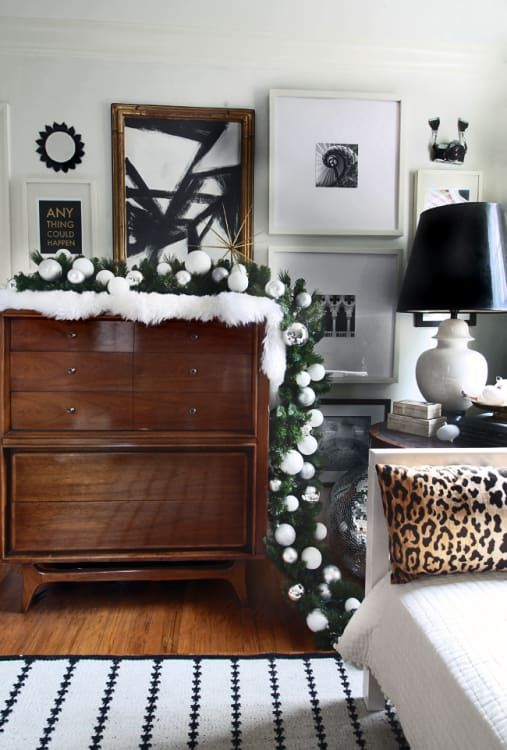 an evergreen Christmas garland with white and silver ornaments integrated can be placed on a dresser