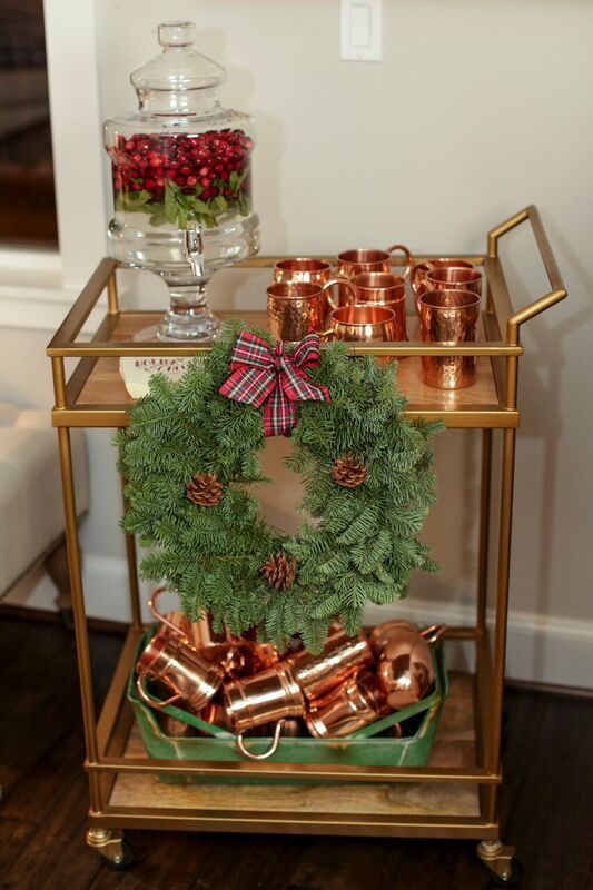 cozy decor with an evergreen and pinecone wreath, copper mugs and a tan with cranberry