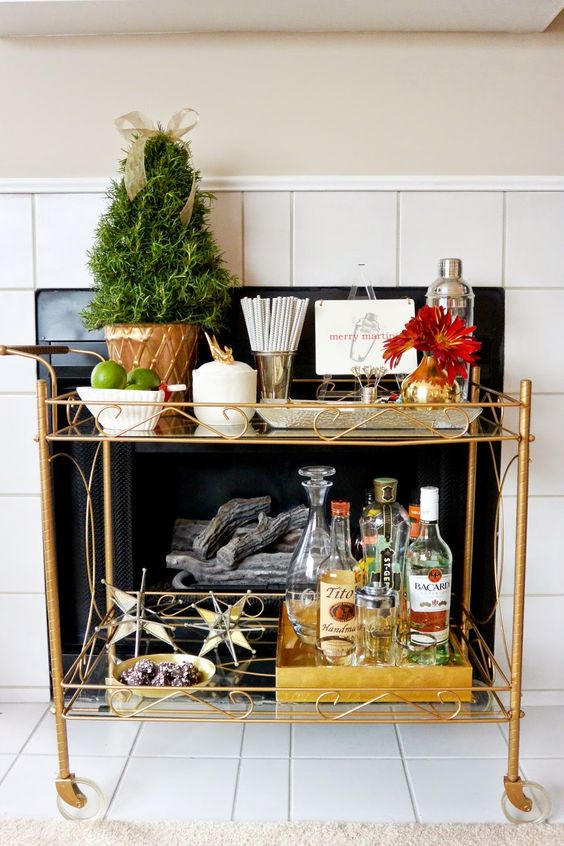 a holiday bar cart with an evergreen tree in a pot and some gilded star ornaments for Christmas