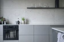 07 a minimalist grey kitchen with sleek cabinets, a grey tile backsplash and floating shelves