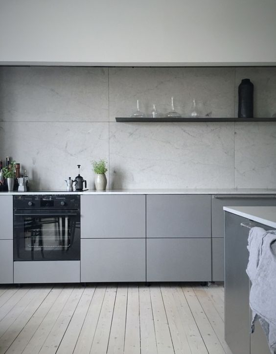 a minimalist grey kitchen with sleek cabinets, a grey tile backsplash and floating shelves