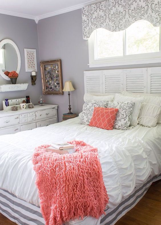 a printed coral pillow and a fluffy blanket give this bedroom a fresh and trendy look at once