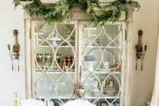 07 cover a china cabinet with an evergreen garland to make your dining space feel like Christmas at once