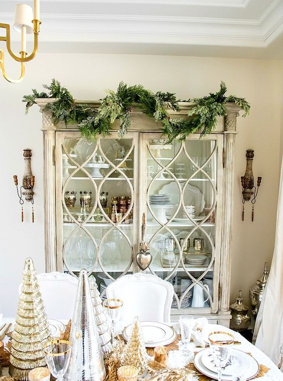 cover a china cabinet with an evergreen garland to make your dining space feel like Christmas at once