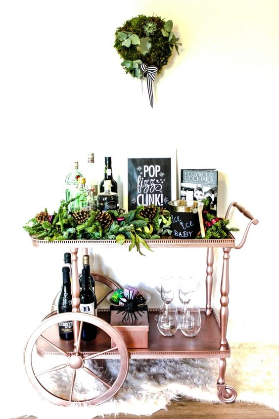 a copper holiday bar cart with lush evergreens, pinecones and a matching wreath over the cart