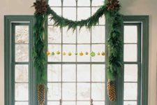 08 decorate a window wit an evergreen Christmas garland, colorful ornaments and large pinecones to make it cooler