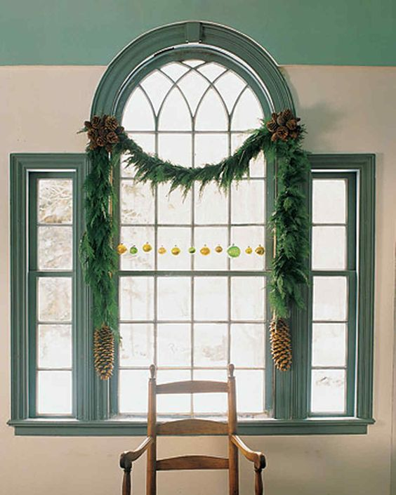 decorate a window wit an evergreen Christmas garland, colorful ornaments and large pinecones to make it cooler