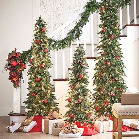 a chic trio of Christmas trees with lights and red ornaments plus a matching garland is a bold idea