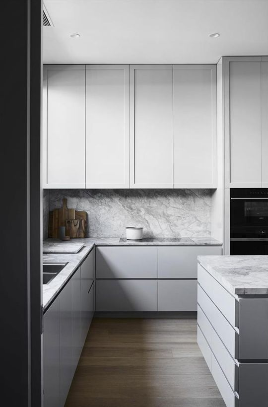 a minimalist kitchen with sleek grey cabinets and a grey marble backsplash and countertops