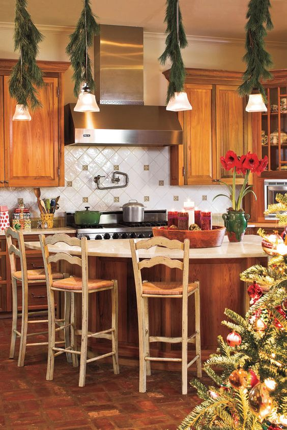 decorate pendant lamps with evergreens to make the kitchen feel more festive