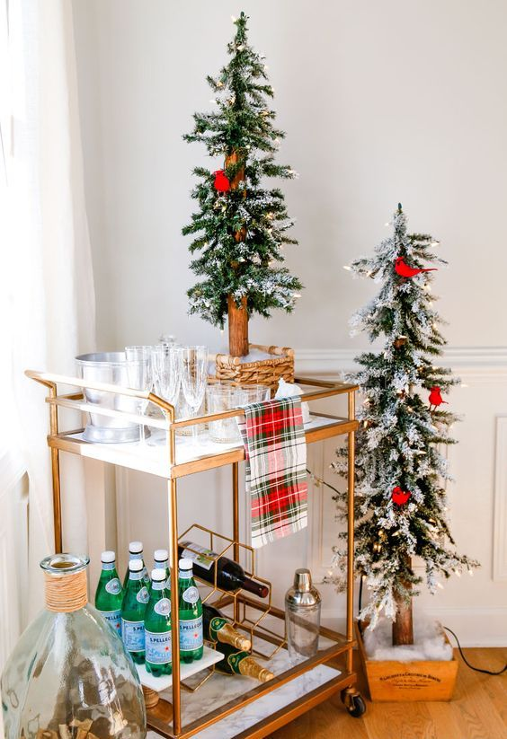 a Christmas cart with a plaid towel and a duo of Christmas trees decorated with red birds