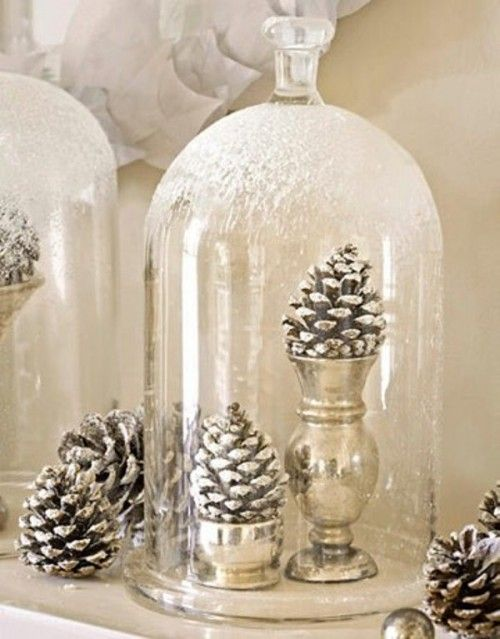 a couple of snowy pinecones in metallic cups in a snowy cloche for a winter wonderland touch