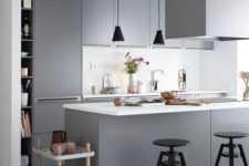 10 a minimalist grey kitchen with sleek cabinets, a white backsplash and touches of black for drama