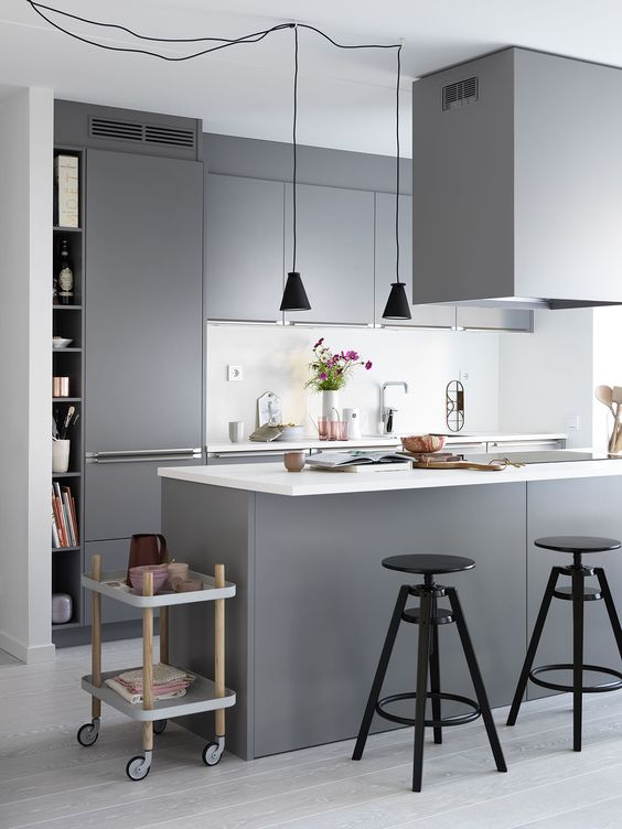 a minimalist grey kitchen with sleek cabinets, a white backsplash and touches of black for drama