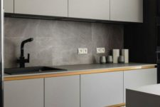 11 a minimalist light grey kitchen with sleek cabinets anad no knobs, grey marble tiles and a matte faucet
