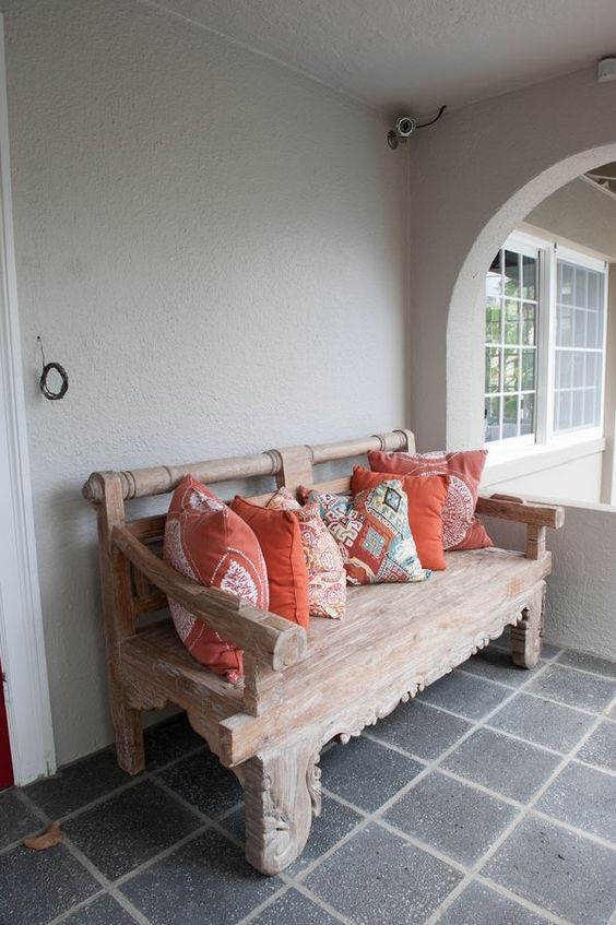 a wabi-sabi entryway bench is styled with bright printed coral pillows to make it trendy