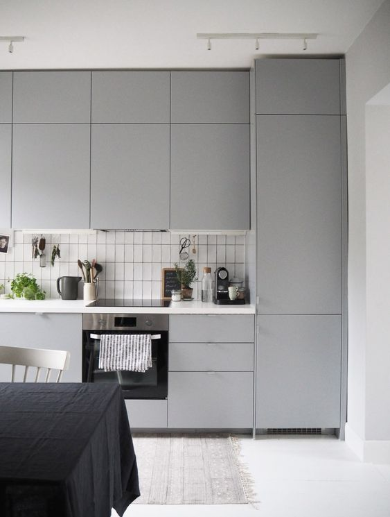 a Scandinavian grey kitchen done with sleek dove grey cabinets and a white backsplash with black grout
