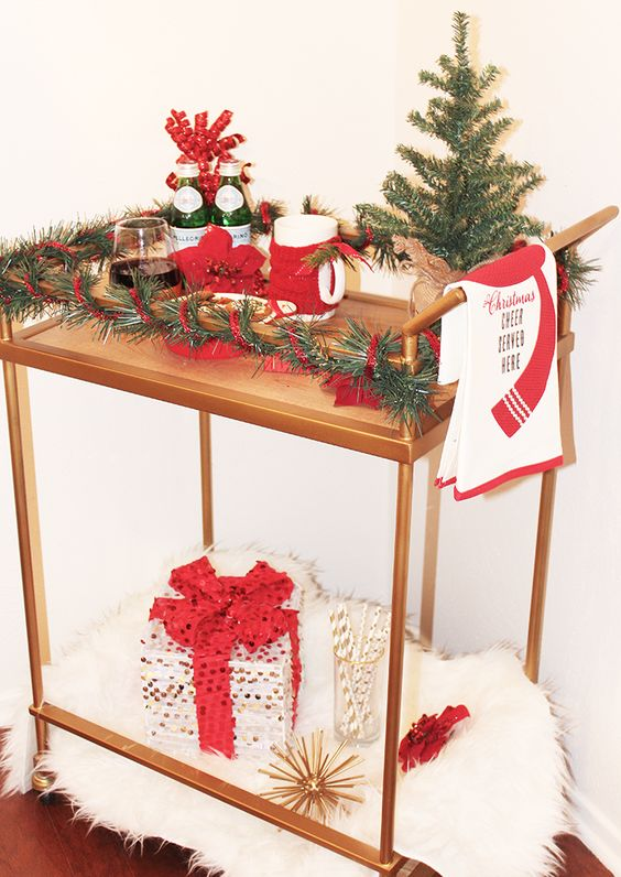 a cute and colorful Christmas bar cart styled with faux fur, a sequin gift, evergreens and red touches