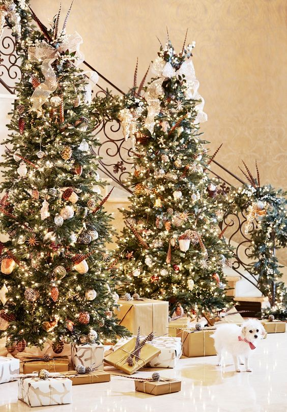 a duo of gorgeous and luxuriously decorated Christmas trees with lights, acorns and other ornaments