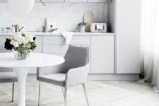 13 a Scandinavian light grey, almost white, kitchen, with a grey marble backsplash and matching upholstered chairs
