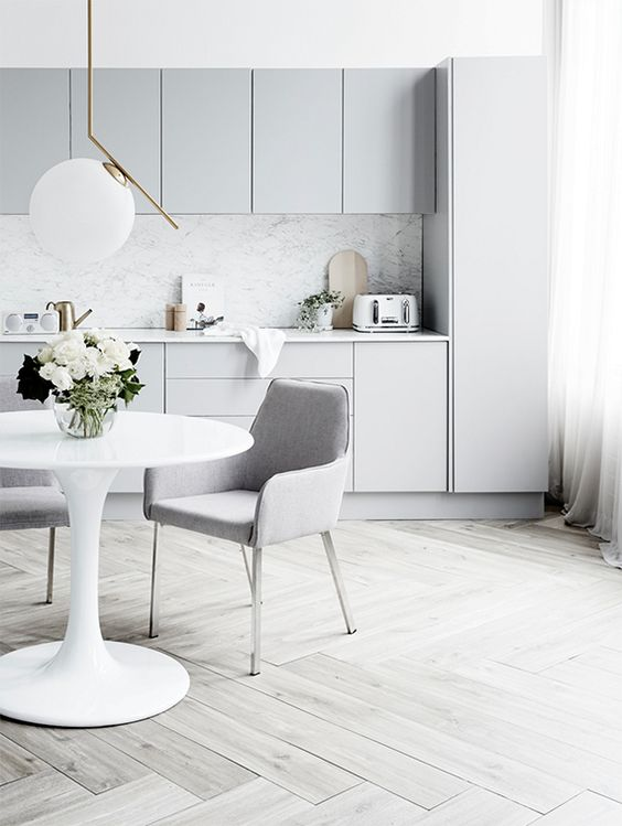 a Scandinavian light grey, almost white, kitchen, with a grey marble backsplash and matching upholstered chairs