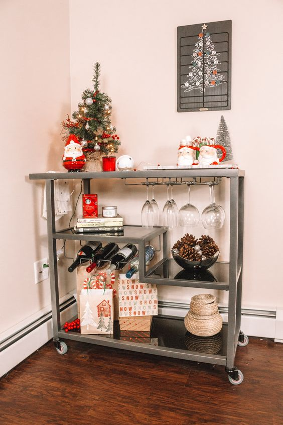 a cute Christmas bar cart with Santa mugs, Christmas trees, pinecones in a bowl and gifts