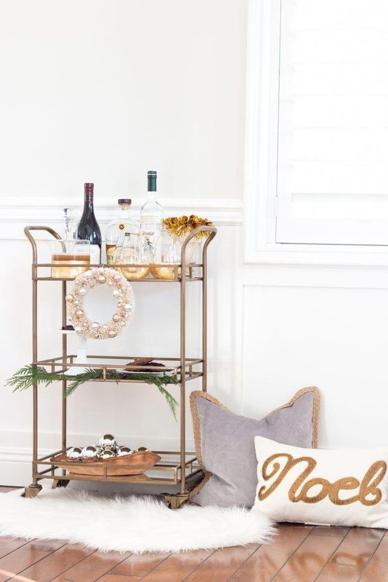 a holiday bar cart with an ornament wreath and a bowl with ornaments plus ferns