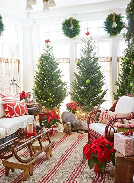 a trio of Christmas trees topped wit red birds and with green ornaments for a cozy space